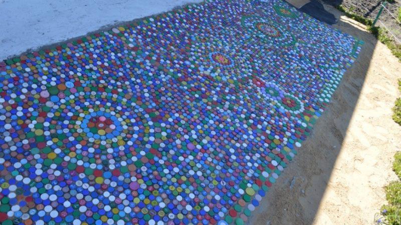 Дорожка из пробок от пластиковых бутылок будет смотреться интереснее, если выложить ее в виде красивого узора.